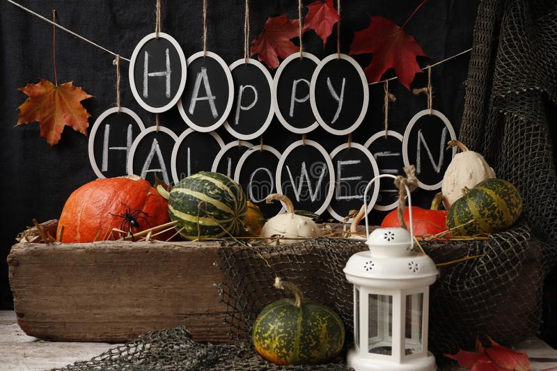 Text `Happy Halloween` and pumpkins. Still life with pumpkins and the text `Happy Halloween` against a white brick wall stock image