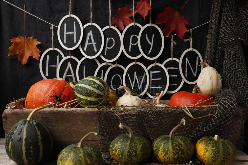 Text `Happy Halloween` and pumpkins. Still life with pumpkins and the text `Happy Halloween` on a dark background royalty free stock images