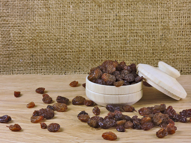 Still life, raisin, wooden bowl royalty free stock image
