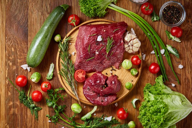 Still life of raw beef meat with vegetables on wooden plate over vintage background, top view, selective focus stock images
