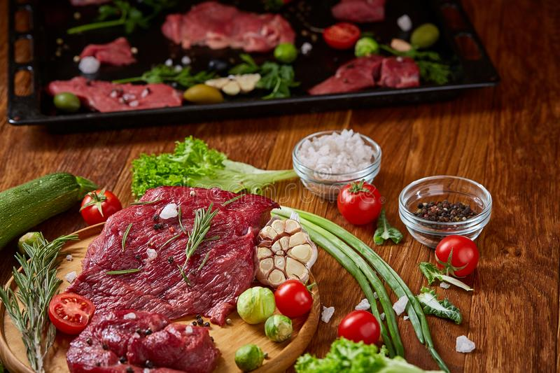 Still life of raw beef meat with vegetables on wooden plate over vintage background, top view, selective focus stock photo