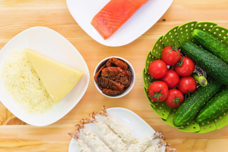 Still life of raw food in white plates on a wooden table. Frozen salmon on a plate next to cucumbers and tomatoes grated royalty free stock photos