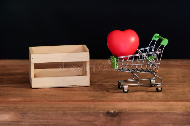 Still life red heart on shopping cart on wood. Table stock photo