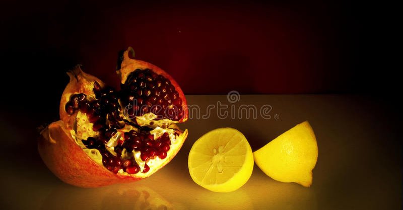 Still life with red pomegranate and lemon. stock photography