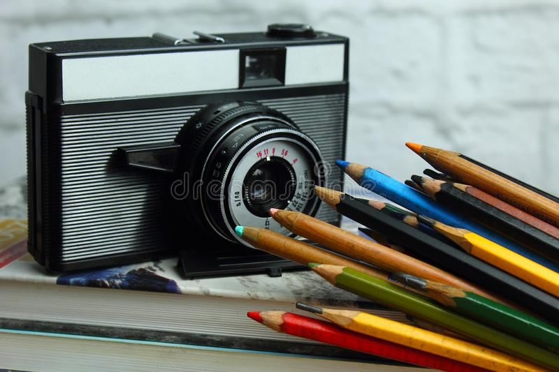 Still life with retro camera. Still life with camera and colorful pencil in fron of white brick wall stock photos