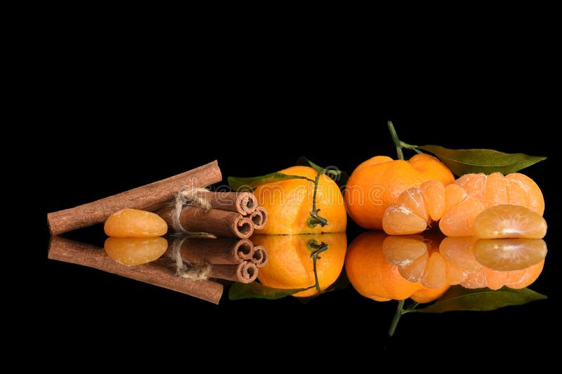 Still life of ripe Christmas tangerines with green leaves, tangerine slices and cinnamon sticks stock photos