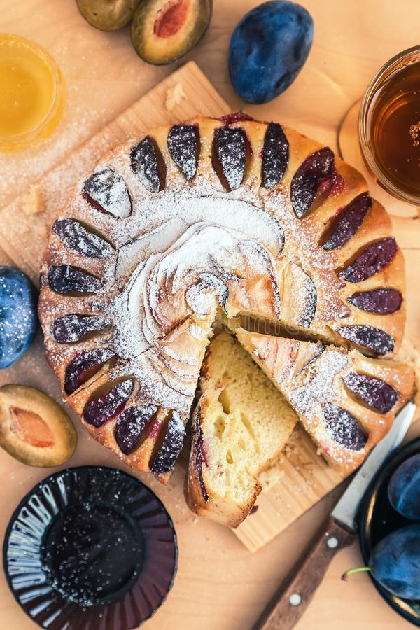 Round plum cake decorated with icing sugar, a cup of black tea and a saucer with fruit. Still life: round plum cake decorated with icing sugar, a cup of black royalty free stock photography