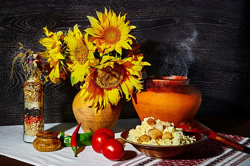 Still life in rural style. Sunflowers in a pot. Porridge with vegetables stock photo