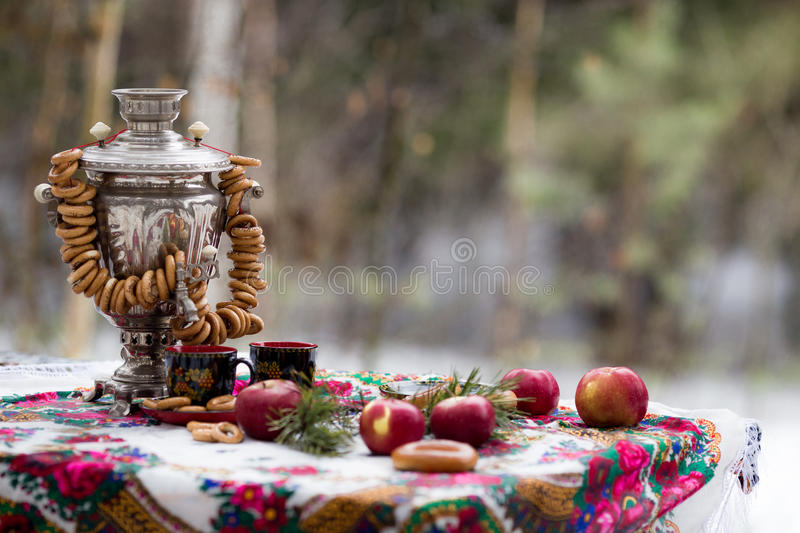 Still Life in the Russian style with a samovar and bagels. Vertical photo still life in the Russian style with apples, donuts, cup on a beautiful tablecloths royalty free stock image