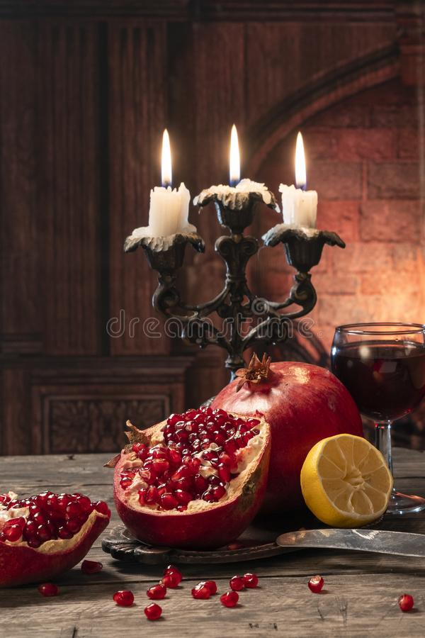 Still life in a rustic style. Fruit-pomegranates, lemon, lying on a wooden table with a glass of wine and candles on the fireplace. Still life in a rustic style royalty free stock image
