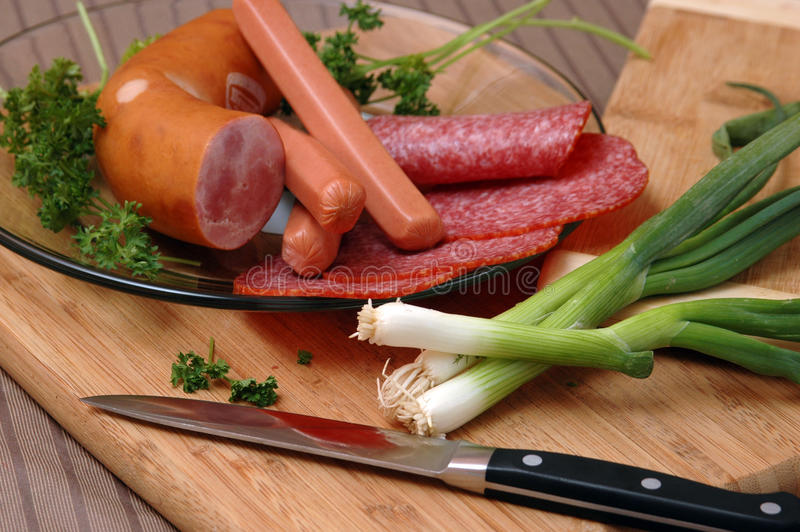 Still life of sausages. On a white plate with verdure royalty free stock image