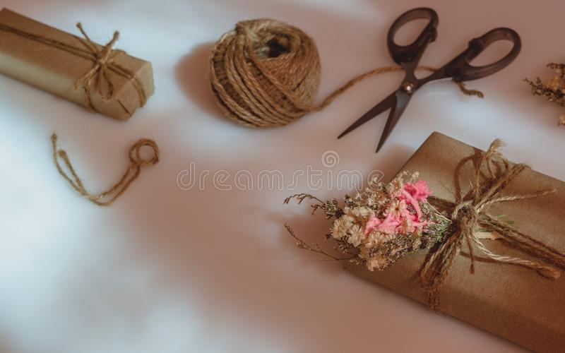 Still life shot of Beautiful small handmade DIY gift box & x28;package& x29; with flowers and decorative rope on white background royalty free stock photos