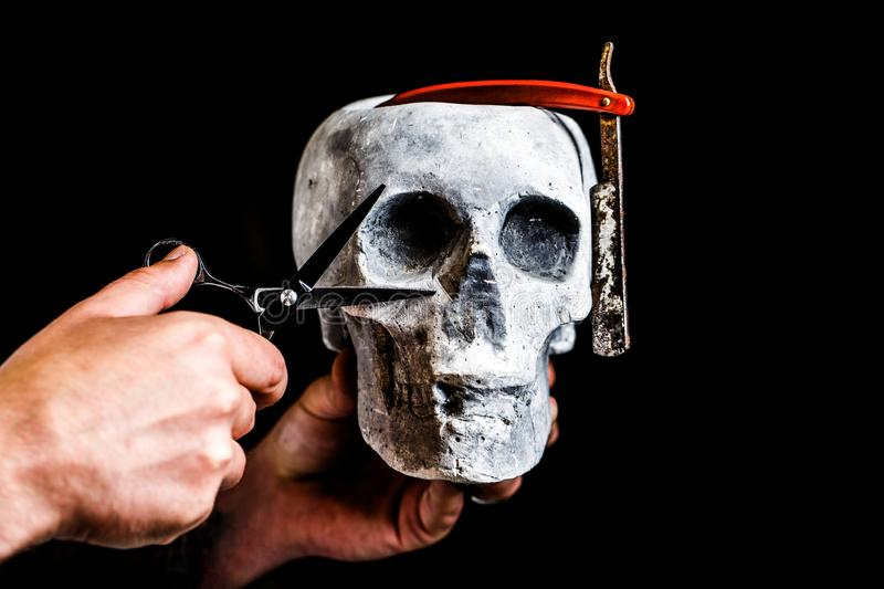 Still life skull with shaving tools. Barber shop tool on black background with copy space. Skull barber. Vintage barber royalty free stock photo