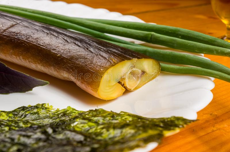 smoked garfish with lime, Basil, green onions, chili, nori chips, spices, olive oil in a white ceramic dish, on a wooden table stock image
