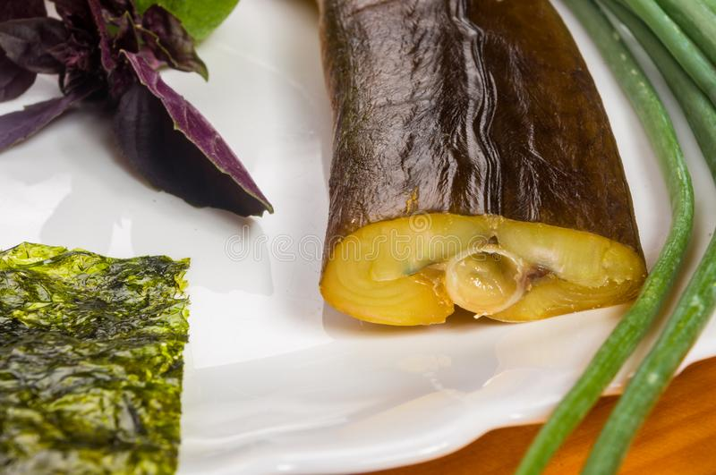 Smoked garfish with lime, Basil, green onions, chili, nori chips, spices, olive oil in a white ceramic dish, on a wooden royalty free stock photos