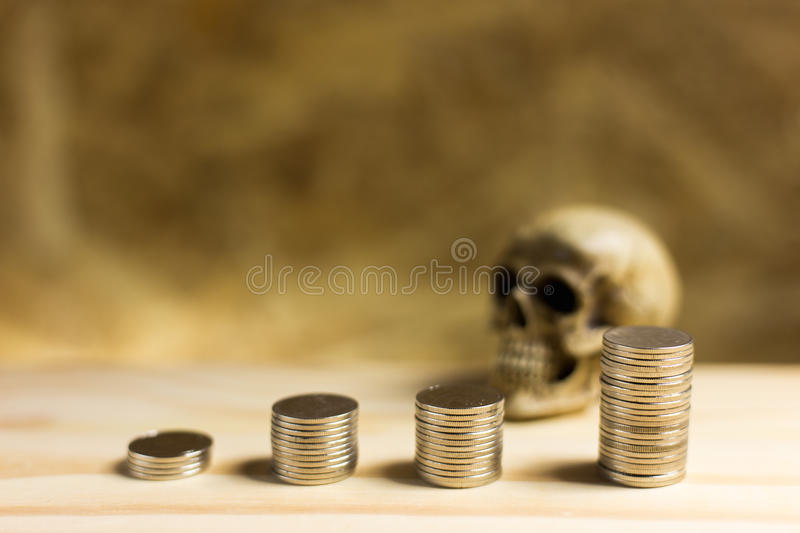 Still life.Staircase of money, Thai coins of one bath on wood an. D skull background.Concept of financial planning and savings royalty free stock photography