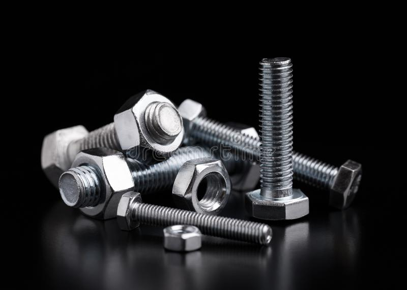 Still life with steel bolts and nuts. Bolts and nuts of different sizes on a black background steel metal industry industrial macro construction concept shape royalty free stock photo