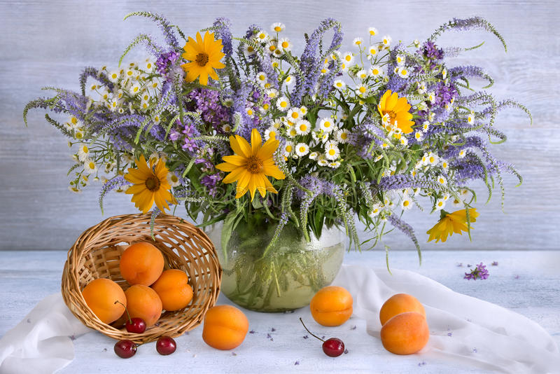 Still life with a summer bouquet, cherries and apricots stock photo