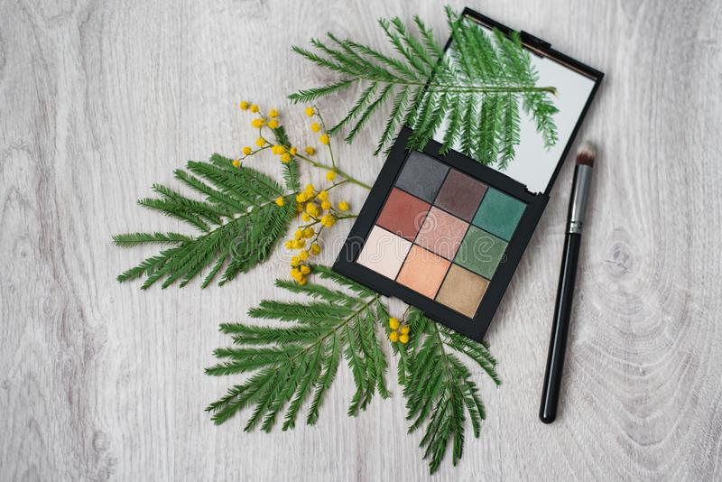 Still life of summer cosmetic make-up, brush and flowers of mimosa on a wooden table. Decor and makeup.  stock photo
