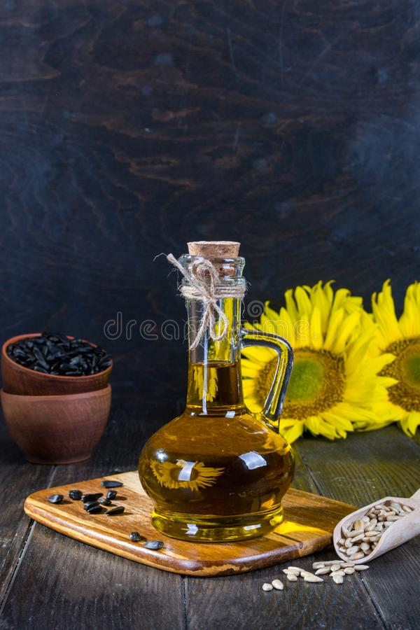 Still life with sunflower oil in glass bottle, seed and sunflower. On the background of wooden boards stock photo