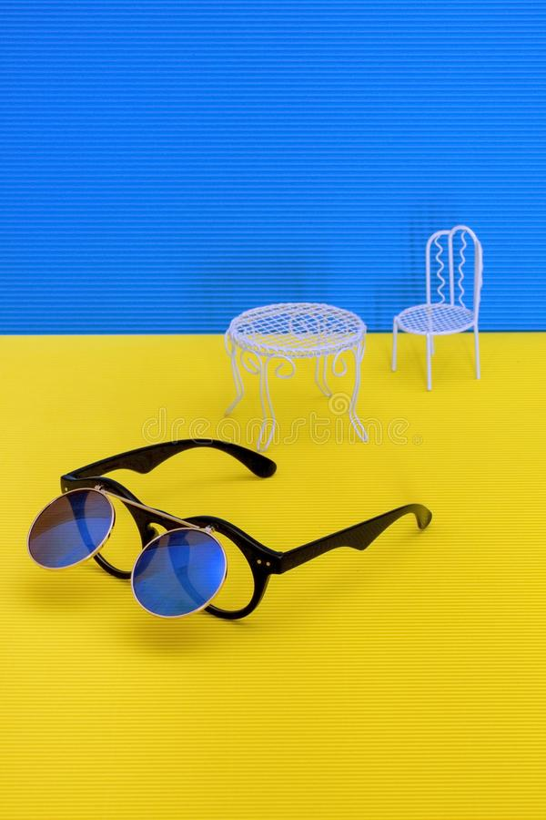 Still life with sunglasses, table and chair stock photo