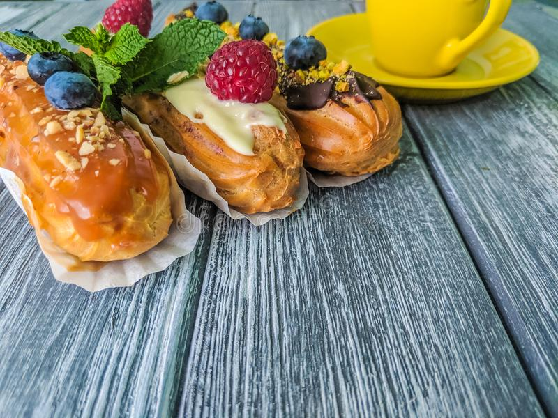 Still life with sweets eclairs with fruits on the wooden background. Strawberry, taste, cakes, caramel, cookie, creme, valentine, raspberry, decoration, eating stock image