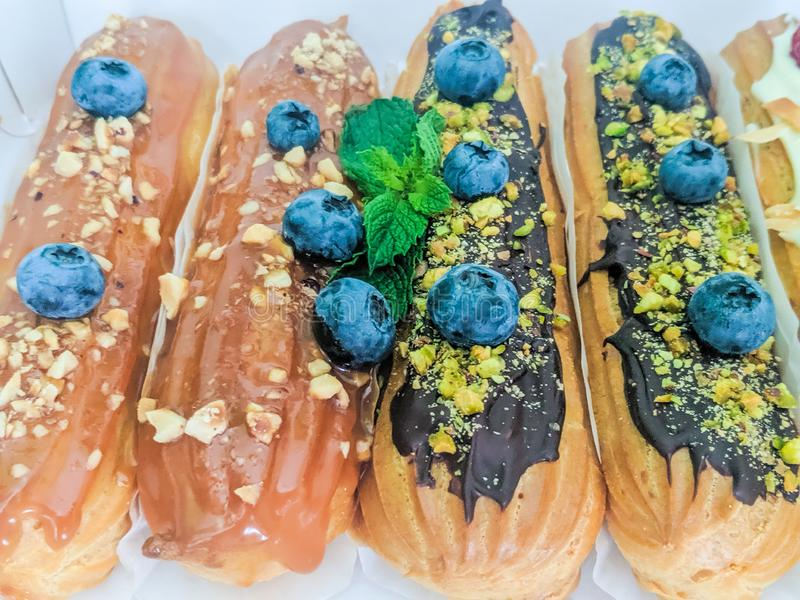 Still life with sweets eclairs with fruits on the wooden background. Strawberry, taste, cakes, caramel, cookie, creme, valentine, raspberry, decoration, eating stock photo