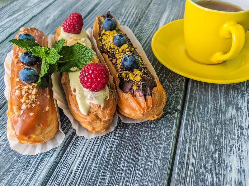 Still life with sweets eclairs with fruits on the wooden background. Strawberry, taste, cakes, caramel, cookie, creme, valentine, raspberry, decoration, eating stock photography