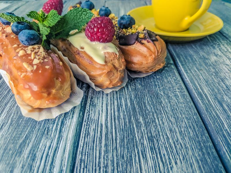 Still life with sweets eclairs with fruits on the wooden background. Strawberry, taste, cakes, caramel, cookie, creme, valentine, raspberry, decoration, eating royalty free stock images