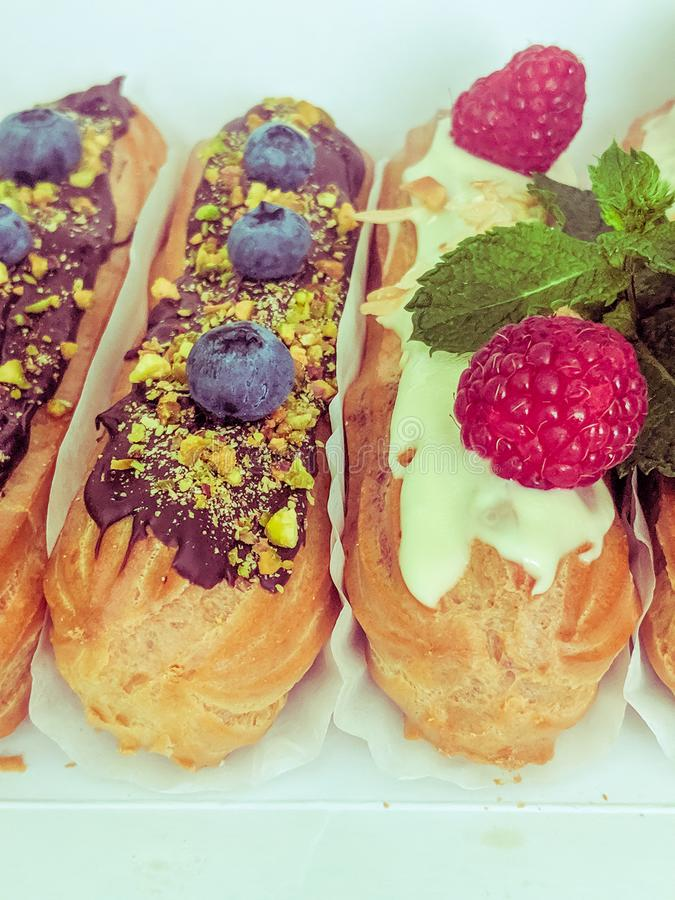 Still life with sweets eclairs with fruits on the wooden background. Strawberry, taste, cakes, caramel, cookie, creme, valentine, raspberry, decoration, eating royalty free stock photos