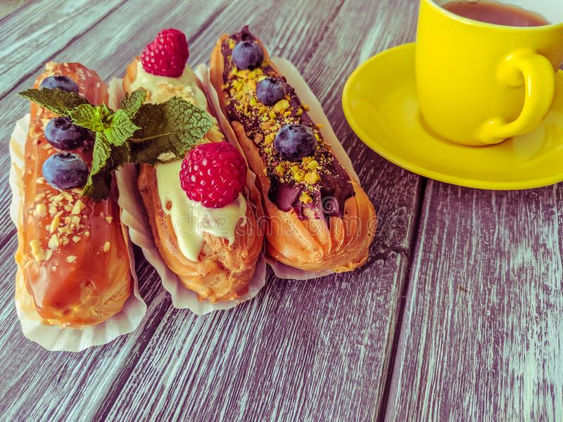 Still life with sweets eclairs with fruits on the wooden background. Strawberry, taste, cakes, caramel, cookie, creme, valentine, raspberry, decoration, eating stock photos