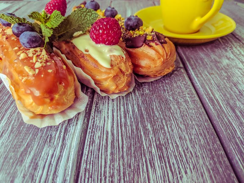 Still life with sweets eclairs with fruits on the wooden background. Strawberry, taste, cakes, caramel, cookie, creme, valentine, raspberry, decoration, eating royalty free stock photo