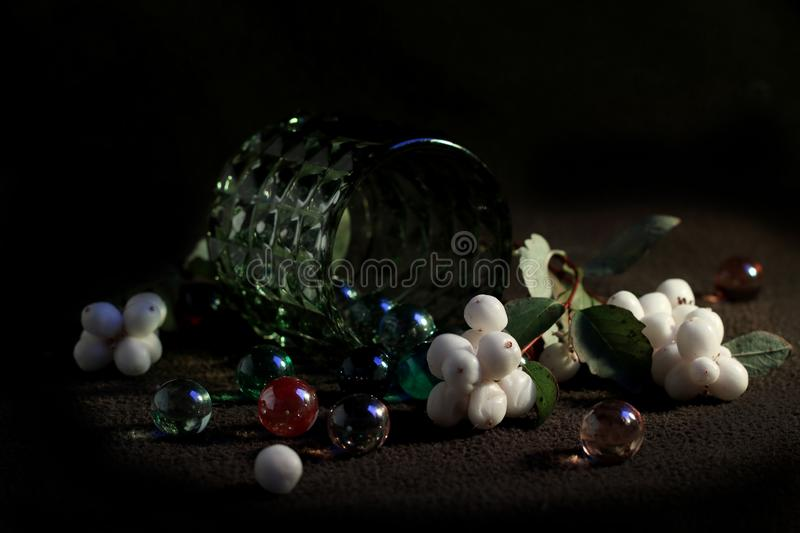 Still life with Symphoricarpos branch and colorful glass balls. Still life with a branch of Symphoricarpos and colorful glass balls on a dark background, in a royalty free stock images