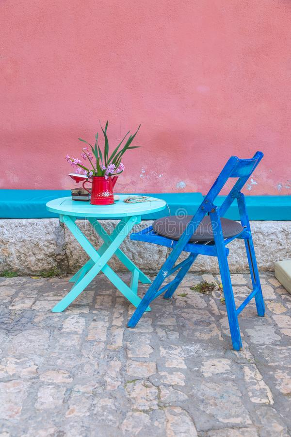 Still life with table and chair at the old color facade. stock images