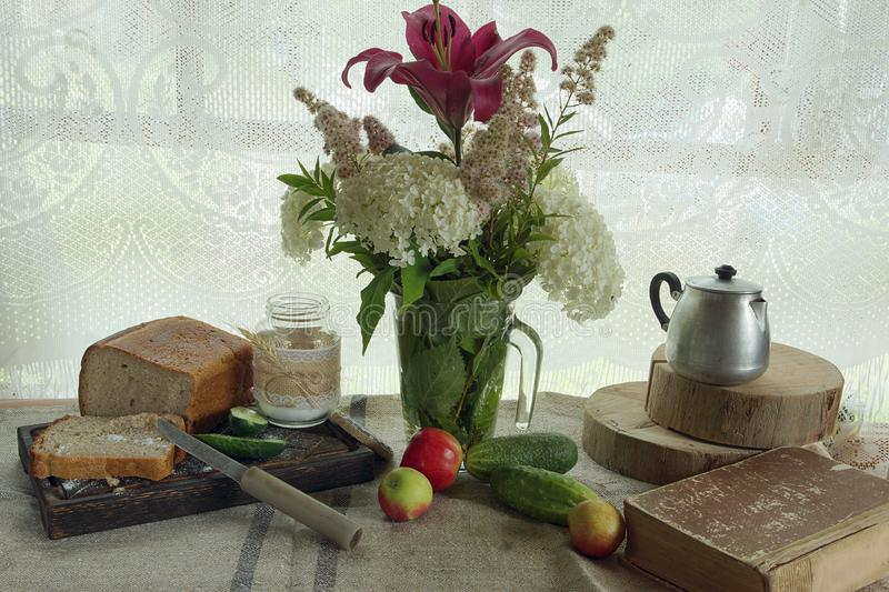 Still life on a table by the window in the village, bread and a cucumber with salt next to a bouquet of flowers stock photos