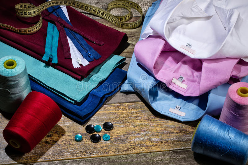 Still Life With Tailor Accessories. Different tailor accessories, pants and shirts on a studio background stock photography