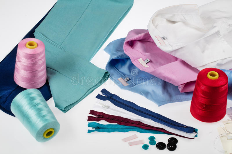 Still Life With Tailor Accessories. Different tailor accessories, pants and shirts on a studio background royalty free stock image
