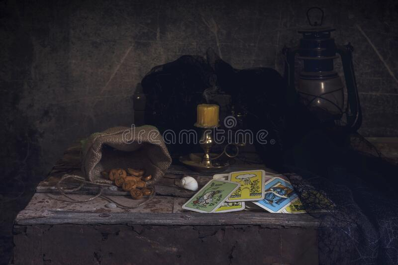 Still Life with tarot cards and runes on a wooden chest. Halloween concept. Still Life with tarot cards and runes on a wooden chest on dark background close-up stock photography