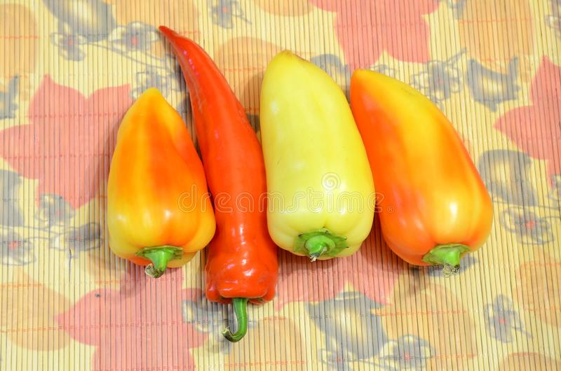 Three sweet peppers and hot peppers lie on a bamboo mat. royalty free stock images