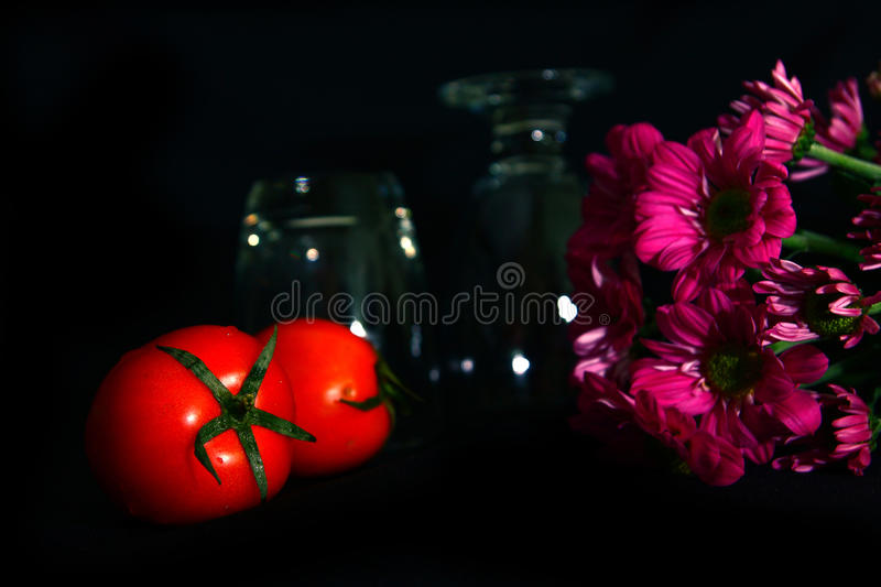 Still life tomatoes , flower. On black background stock photography