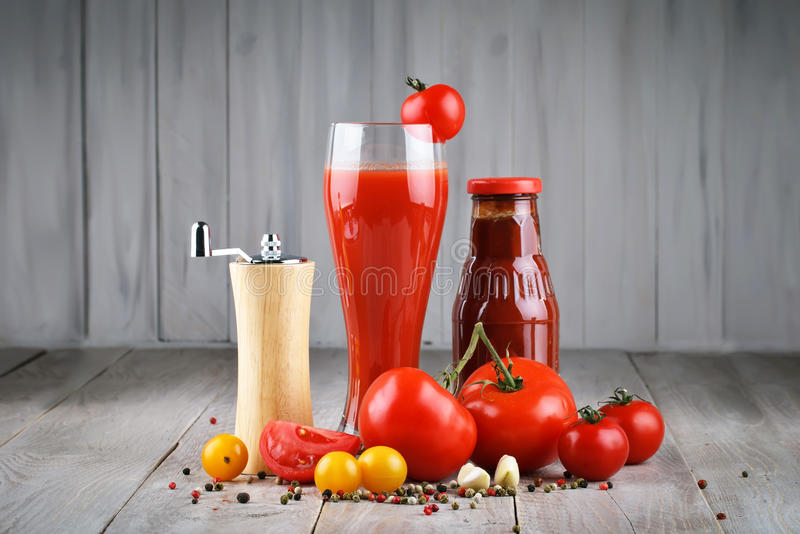 Still life of tomatoes, garlic, tomato juice and tomato sauce on wooden boards. royalty free stock photography