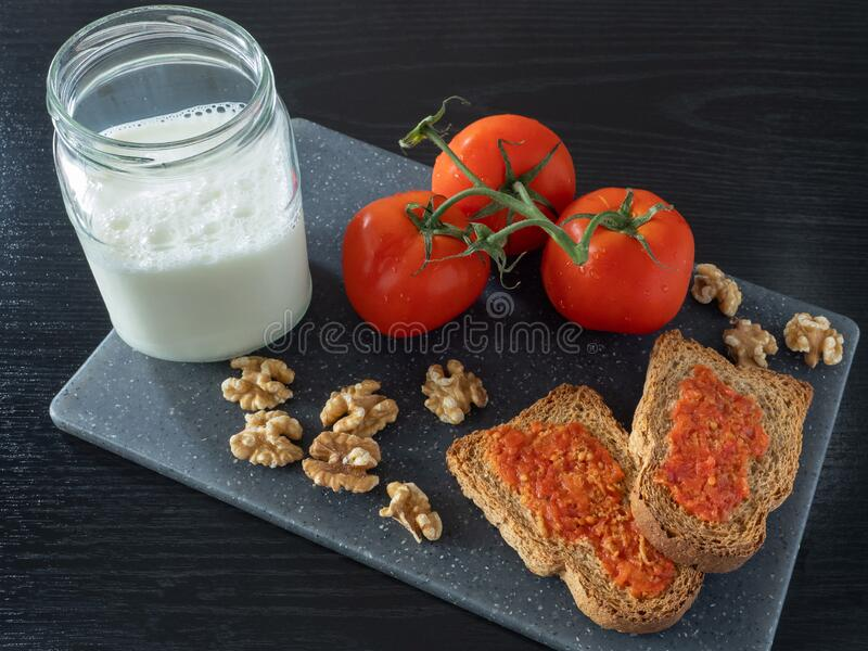 Still life of tomatoes with toasts, onions and garlic royalty free stock image