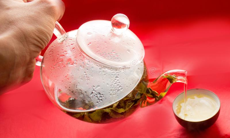 Still life, transparent glass teapot, cup with tea, pour tea from a teapot into a cup. Still life, clear glass teapot with tea on a black background, pour tea stock photography