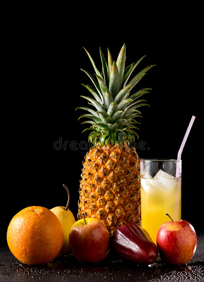 Still life tropical fruits and glass of juice. Composition with tropical fruits and glass of juice on a black reflective background with drops of water, Studio royalty free stock images
