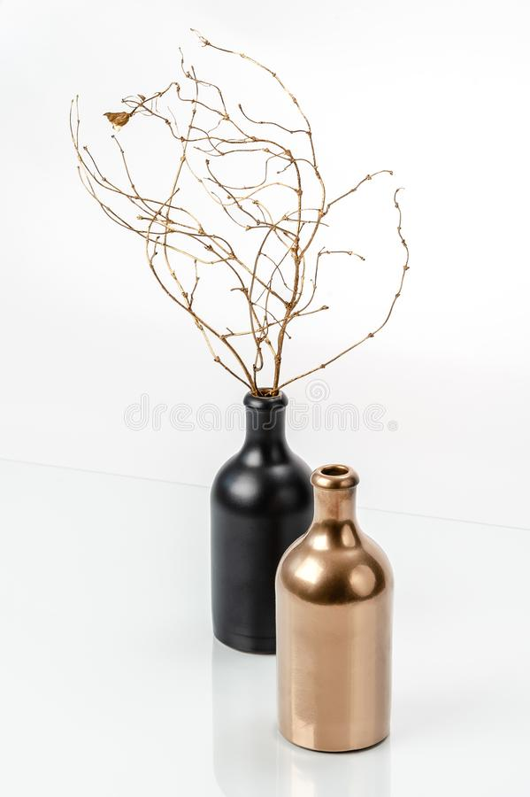 Still life with two bottles and golden branches in a minimalist style. Still life with two bottles and golden branches in minimalist style royalty free stock image