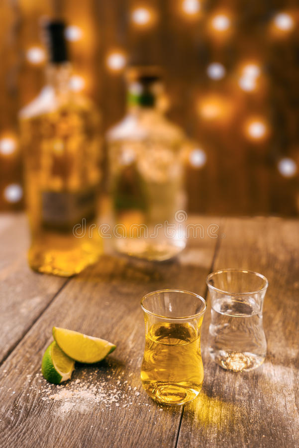 A still life of two shots of tequila. A shot of blanco and a shot of anejo tequila displayed on a wood background royalty free stock image