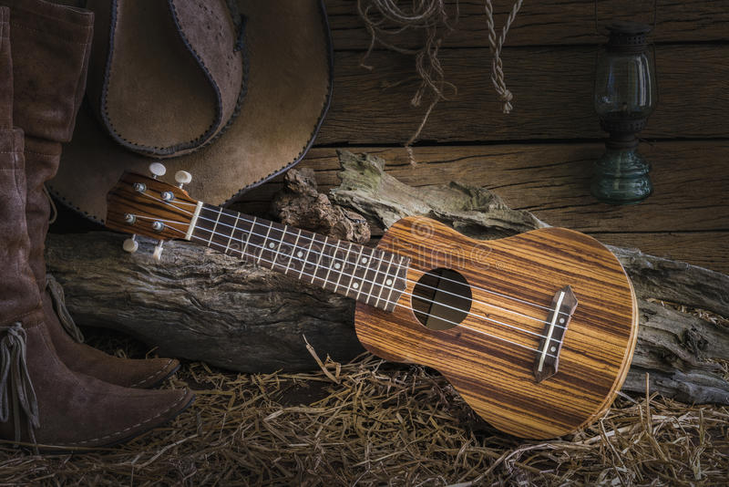 Still life with ukulele on cowboy hat and traditional leather bo stock photo