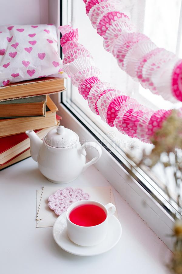 Still life of used candles, tea, teapot, pillow and pink paper garland, books on a white table near window, romance morning. Feminine concept royalty free stock photos