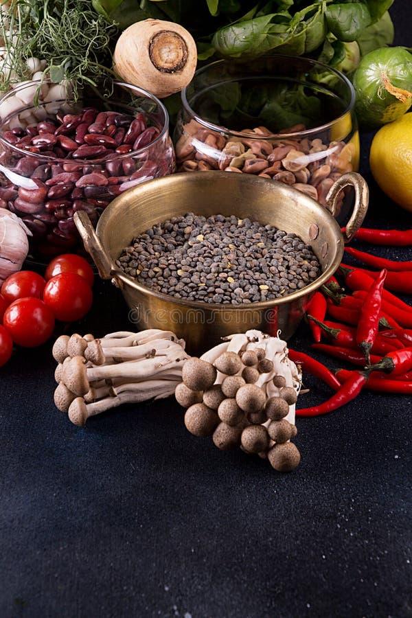 Still life vegan food set on dark background. Concept healthy eating. Beans, lentils, chili, nut, cucumber, spinach, mushrooms shimidzhi, cherry tomato royalty free stock image