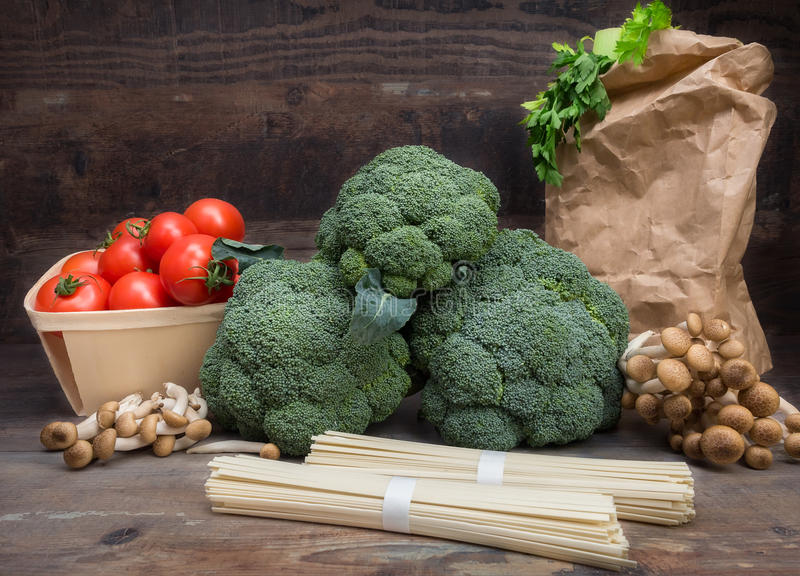 Still life vegetables cabbage broccoli with tomatoes mushrooms spaghetti green leaves wooden background royalty free stock image